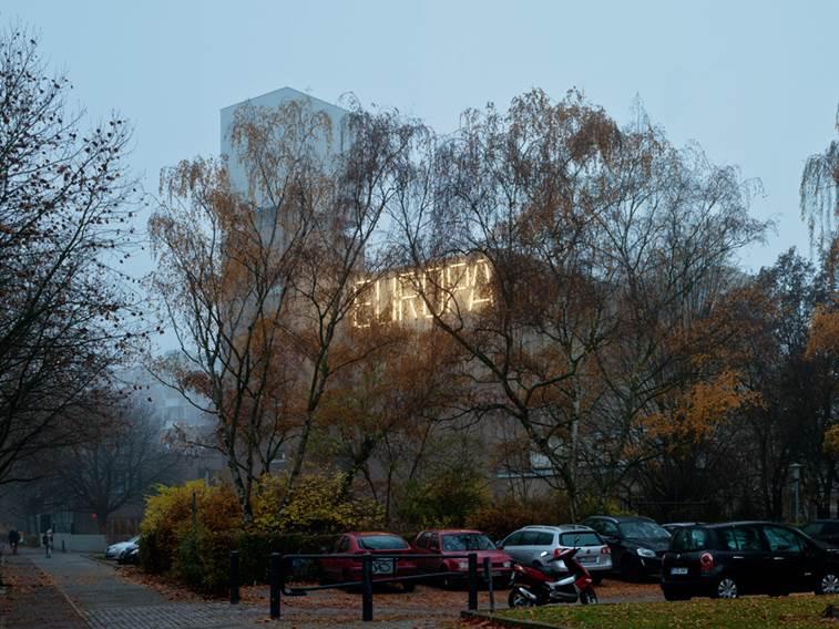 Durch kahle Bäume scheinen Leuchten, die das Wort Europa an einer Hauswand formen-