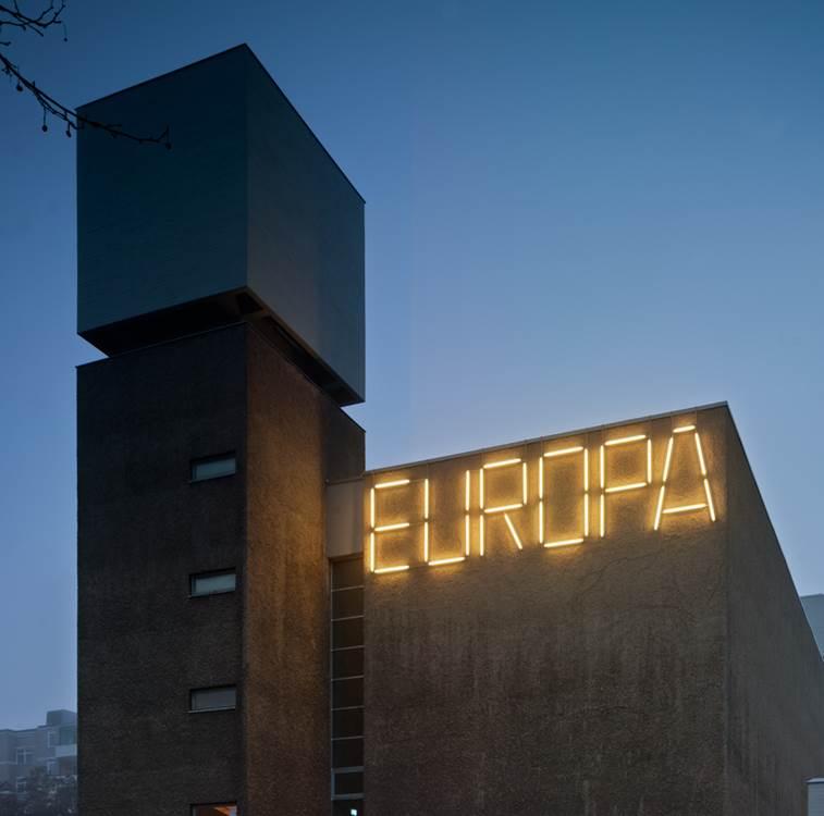 Leuchten formen das Wort Europa an der Seite einer Hauswand im Halbdunkel